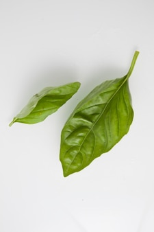 Various green vegetables on a light background, top view