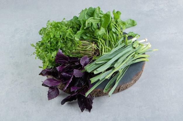 Различные зеленые овощи на доске, на мраморе.