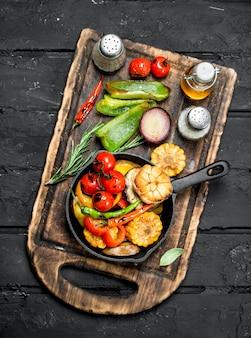 Различные овощи-гриль в сковороде со специями на деревянной доске на темном деревенском столе.