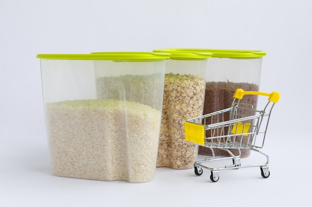 Various groats in containers or jars and grocery cart. rice oatmeal and buckwheat