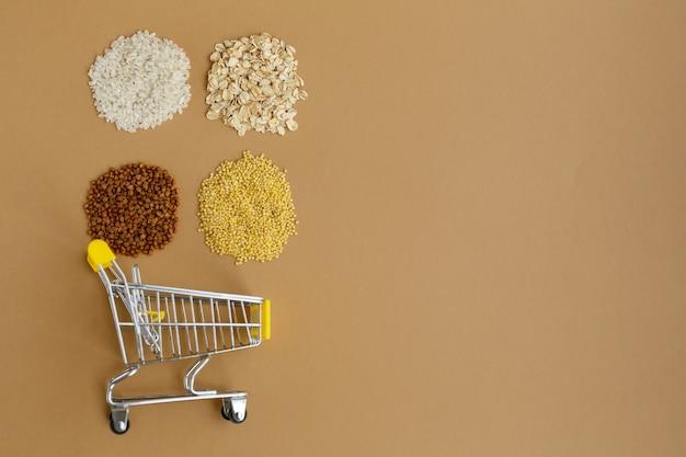 食料品のカートのさまざまなひき割り米とオートミール ソバとキビ