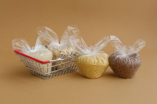 茶色の表面の食料品バスケットのパッケージのさまざまな割り。米とオートミール、そばとキビ