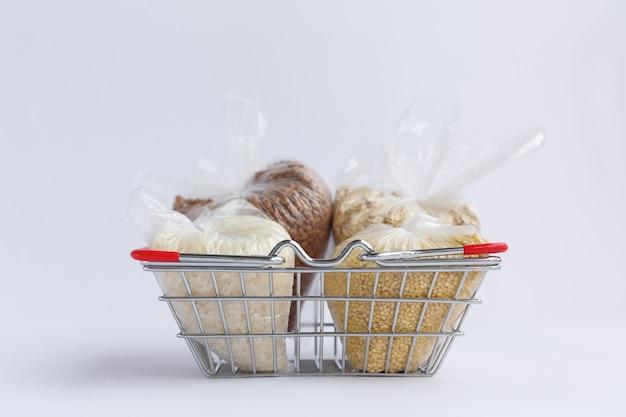 白い表面の食料品バスケットのパッケージのさまざまな割り。米とオートミール、そばとキビ