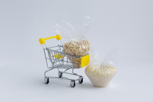 白い表面の食料品のカートのパッケージのさまざまな割り。ご飯とオートミール