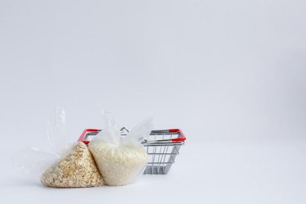 食料品のバスケットの近くのパッケージのさまざまなひき割り米とオートミール