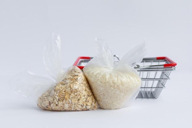 白い表面の食料品バスケットの近くにあるパッケージのさまざまな割り。ご飯とオートミール