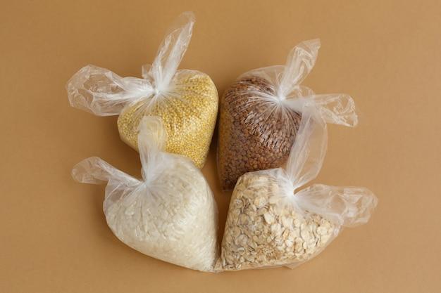 갈색 표면에 작은 비닐 봉지에 다양한 가루. 쌀과 오트밀, 메밀과 기장