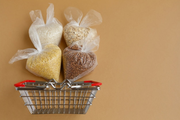Various groats in packages in grocery basket. rice and oatmeal buckwheat and millet