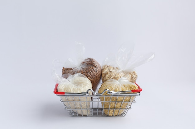 Various groats in packages in grocery basket rice and oatmeal buckwheat and millet