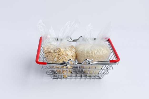 Various groats in packages in grocery basket. rice and oatmeal