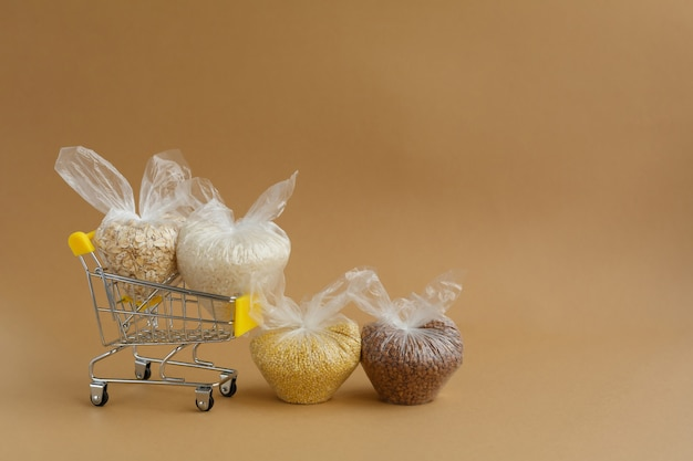 Various groats in packages in grocery cart rice and oatmeal buckwheat and millet