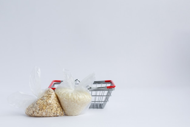 Various groats in packages near grocery basket rice and oatmeal
