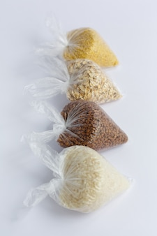 Various groats in small plastic bags on a white background. rice and oatmeal, buckwheat and millet