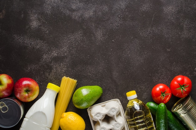 Various groceries on dark concrete background. food delivery concept. food donations.