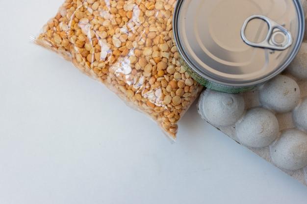 패키지 평면도의 다양한 식료품 제품. 파란색 배경에 종이 봉지에 파스타, 시리얼, 통조림 식품. 음식 배달, 기부 또는 재고 제공 개념. 공간을 복사합니다.
