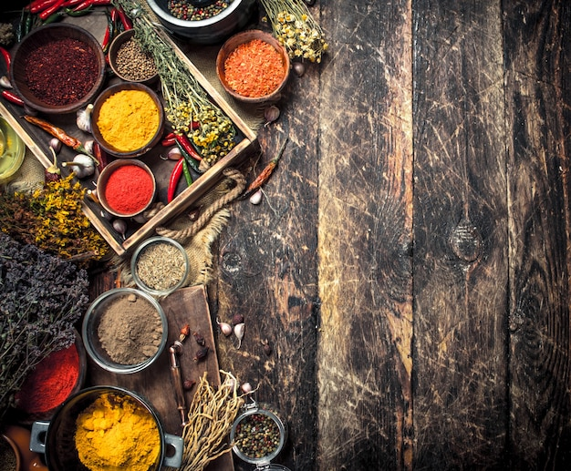 Various ground spices and herbs in an old tray. on a wooden background.