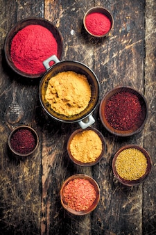 Various ground spices and herbs. on a wooden background.