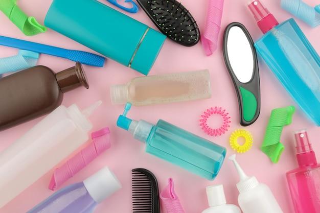 Различные средства по уходу за волосами и аксессуары для волос на ярко-розовом фоне. косметика для волос. вид сверху с местом для текста. фон