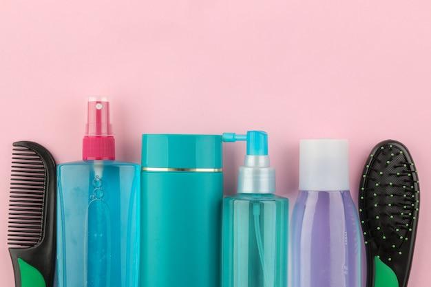 Различные средства по уходу за волосами и различные аксессуары для волос на ярко-розовом фоне. косметика для волос. вид сверху с пространством для текста