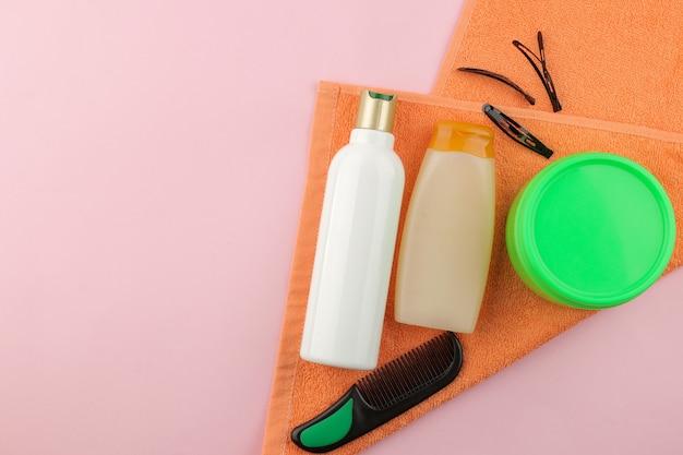明るいピンクの背景にさまざまなヘアケア製品とさまざまなヘアアクセサリー。ヘア化粧品。テキスト用のスペースのある上面図