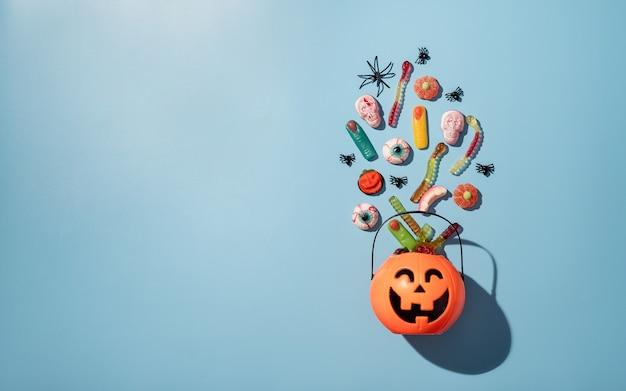 青い固体背景のカボチャ鍋で様々なハロウィーンのお菓子やキャンディー