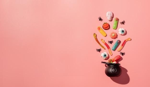 ピンクの無地の背景に黒い鍋にさまざまなハロウィーンのお菓子