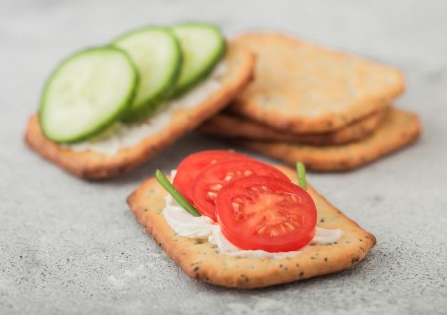 軽い台所のテーブルの上にクリームとキュウリとトマトの様々な健康的なクラッカー