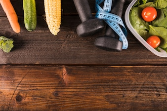 Various healthy food with measuring tape and dumbbell on wooden backdrop