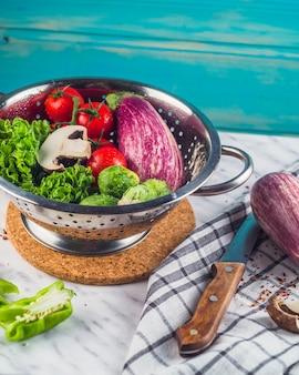 Различные здоровые овощи в дуршлаге над мраморной столешницей
