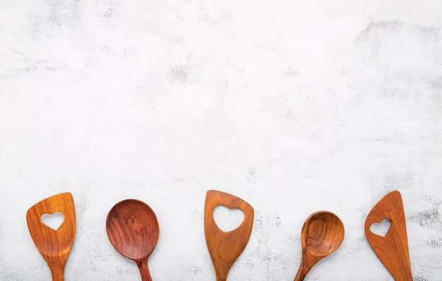 平らな敷設とコピースペースを持つ白いコンクリートの背景に木製の調理器具のさまざまなハートの形