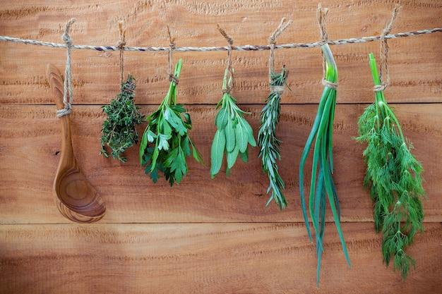 Различные травы, висящие на потрепанный деревянный фон для концепции приправы.