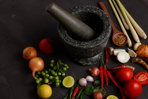 Various herbs, spices and ingredients on dark.