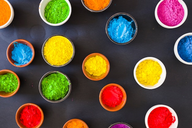 Various holi color powder in the bowl on black background