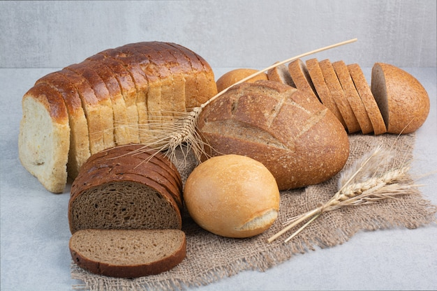 Various homemade bread on burlap with wheat. high quality photo