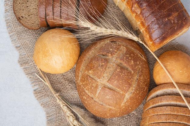 Различный домашний хлеб на мешковине с пшеницей. фото высокого качества