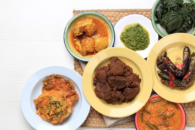 Различные домашние блюда масакан паданг или минанг на белом фоне с копией пространства. популярно как наси паданг.
