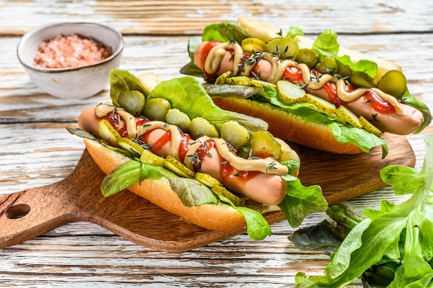 Various hot dog with vegetables, lettuce and condiments. white wooden background. top view.