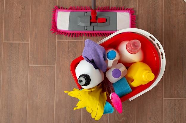 Различные бытовые моющие средства и бутылки в пластиковом ведре на полу