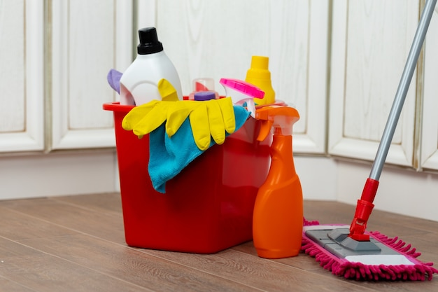 床にあるプラスチック製のバケツに入ったさまざまな家庭用洗剤とボトル