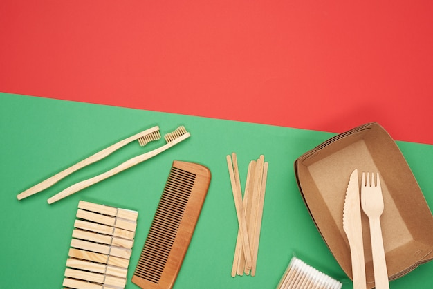 Various household items from recyclable raw materials on a green background, top view, zero waste