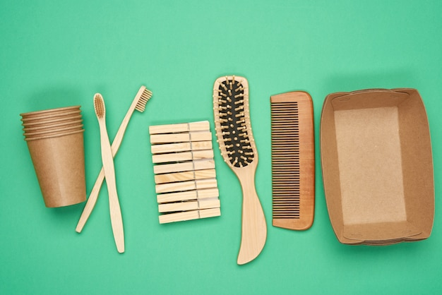 Various household items from recyclable raw materials on a green surface, top view, zero waste