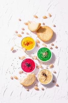 다양한 후무스 딥, 시금치, 비트 뿌리, 심황, 야채, 비건 스낵과 함께 다양한 색상의 후무스가 평평하게 놓여 있습니다. 흰색 퍼티 배경, 상위 뷰