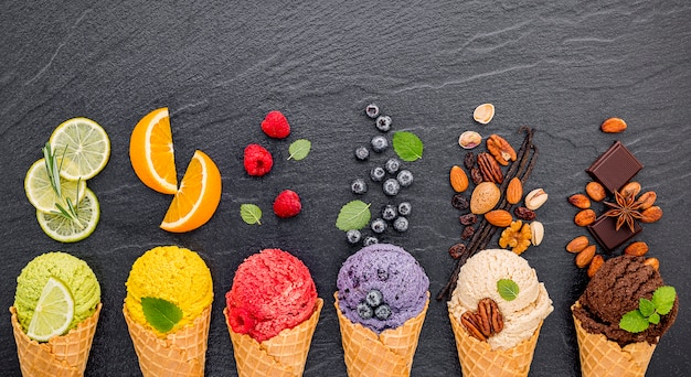 Various of ice cream flavor in cones set up on dark stone