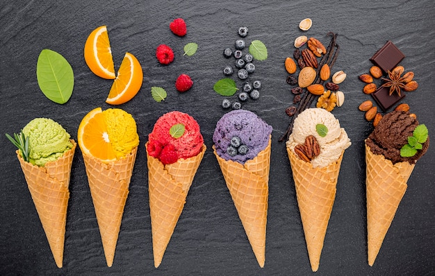 Various of ice cream flavor in cones set up on dark stone