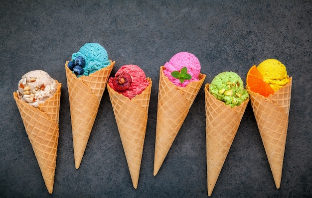 Various of ice cream flavor in cones setup on dark stone background .