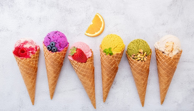 Various of ice cream flavor in cones setup on white stone background .