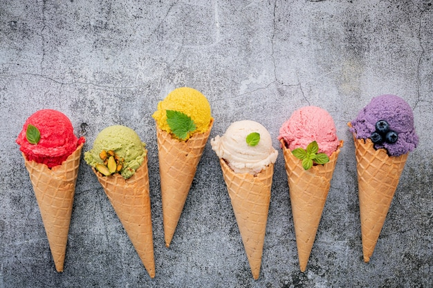 Various of ice cream flavor in cones with berries in wooden box setup on concrete background
