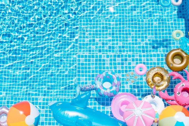 Various inflatable on a pool water background ball crab dolphin float summer and travel