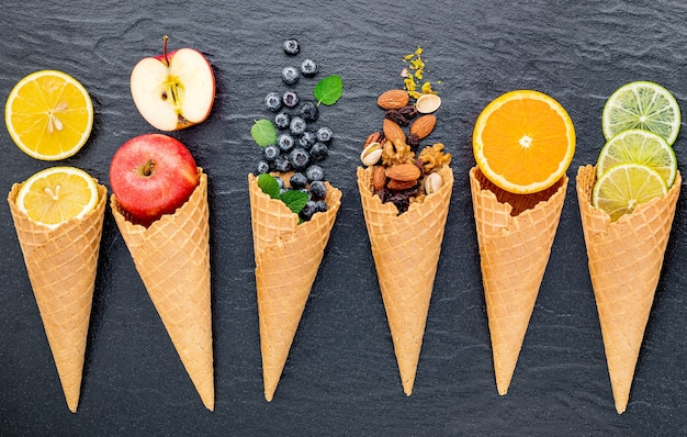 Various of ingredient for ice cream flavor in cones set up on dark stone background .