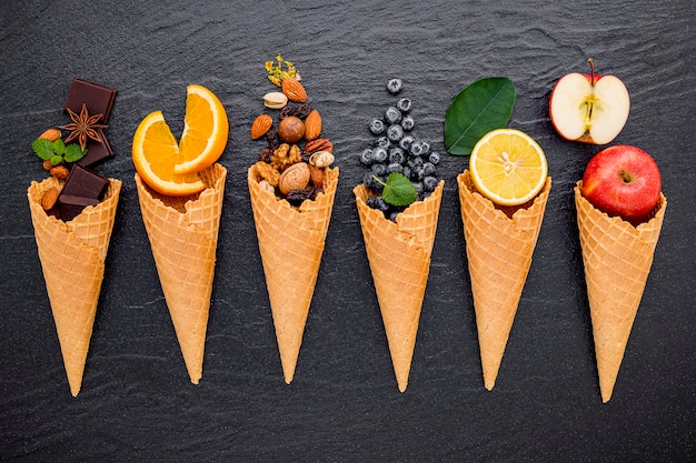 Various of ingredient for ice cream flavor in cones set up on dark stone